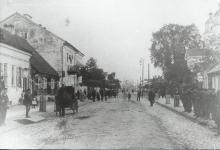 Zdjęcie czarno-białe  ukazujące fragment  ulicy Rynek Zygmunta Augusta, po prawej stronie widoczna słabo część augustowskiej cerkwi a na chodniku stoi grupa mężczyzn, natomiast po lewej stronie po ulicy jedzie dorożka oraz widać w oddali spacerujących ludzi.