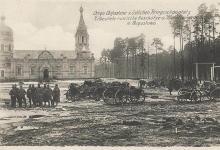 Zdjęcie czarno- białe z początku XX wieku ukazujące centrum Augustowa podczas I Wojny Światowej,na tle cerkwi po lewej stronie stoi grupa dziewięciu żołnierzy, pozująca do zdjęcia a po prawej stronie jest dużo armat.