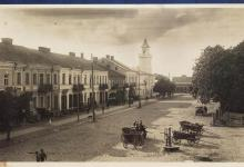 Zdjęcie czarno- białe ukazujące pierzeję południową ulica Rynek Zygmunta Augusta, na pierwszym planie po prawej stronie jest kilka drewnianych wozów konnych czyli furmanek - na dwóch są ludzie a po lewej są augustowskie kamieniczki- w oddali widoczny ratusz oraz spacerujący ludzie.