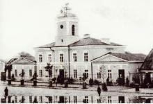 Zdjęcie czarno- białe ukazujące augustowski ratusz w1903 r., przed ratuszem jest kilka osób stojących oraz spacerujących.