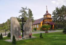 Na pierwszym planie po lewej stronie jest krzyż prawosławny  a po jego obu stronach są pomniki, natomiast na drugim planie po prawej stronie jest Molenna w Gabowych Grądach, przypomina wyglądem budynek cerkwi prawosławnej, fot. J. Koniecko
