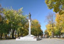 Kolumna Zygmunta Augusta na tle jesiennego parku,przy kolumnie jest kilka spacerujących osób, fot. J. Koniecko