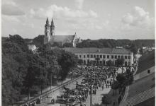 Zdjęcie czarno- białe z początku XX wieku przedstawiające widok z ratusza na ulicę  Rynek Zygmunta Augusta .Na tle augustowskich kamieniczek jest tłum ludzi, widoczne są także przy nich konie a w oddali wystające wieże augustowskiej bazyliki.Po lewej stronie widocznych jest kilka dużych drzew.