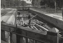 Zdjęcie czarno-białe przedstawiające spław drewna na Kanale Augustowskim w trakcie śluzowania na Śluzie Augustów w 1930 roku, widoczny na pierwszym planie flisak na tratwie.