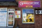 Zdjęcie z zewnątrz , nad oknem zawieszony duży szyld w kolorze fuksja- fiolet z białymi napisami Wakasyjny Świat Doradcy Turystyczni oraz mały napis w kolorze fioletowym na pomarańczowym tle Bial- Tur, na ścianie budynku tablica z ofertami turystycznymi, na zdjęciu sa zamknięte drzwi do biura a po lewej stronie zdjęcia jest biały duży szyld , przymocowany do ściany budynku z niebieskimi i czerwonymi napisami: Biuro Turystyki Bial- Tur, oferujemy bilety:lotnicze, autokarowe, promowe, tanie linie, wizy,wczasy