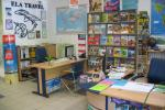 Wnętrze biura podróży, na ścianie duży, czarny napis Ela Travel, dodatkowo na ścianie są mapy, plakaty, dyplomy;meble biurowe są w kolorze jasno brązowym z elementami granatowymi, dwa biurka i krzesła oraz wysoka półka z katalogami wycieczek a na niższych regałach stoją segregatory.